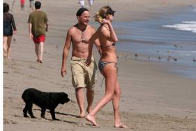 Charlize Theron plays with a male companion and her dogs on the beach in Malibu, CA